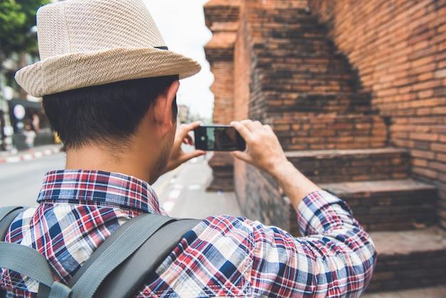 Viaggiatore con zaino e sacco a pelo turistico maschio asiatico che prende foto con lo smartphone a tha phae gate, uno degli antichi punto di riferimento famoso della città di chiang mai tailandia