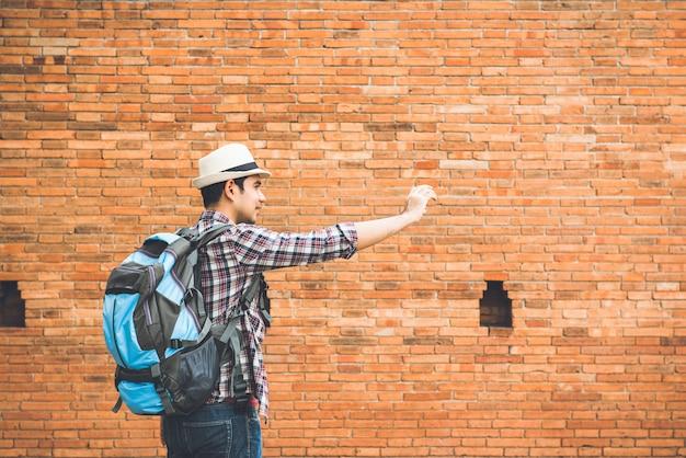 Viaggiatore con zaino e sacco a pelo turistico maschio asiatico che prende selfie alla parete del portone di tha phae, uno del punto di riferimento antico della città in chiang mai thailand