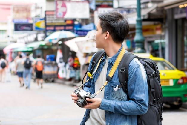 Viaggiatore con zaino e sacco a pelo turistico maschio asiatico che viaggia in strada di khao san, bangkok, tailandia