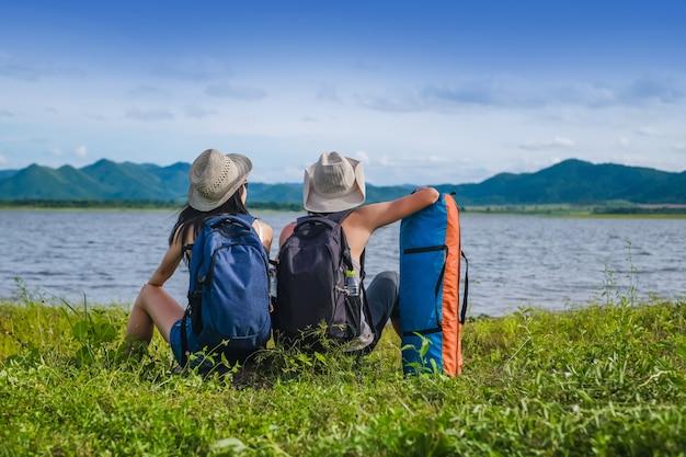 Viaggiatore coppia seduta vicino al lago in montagna