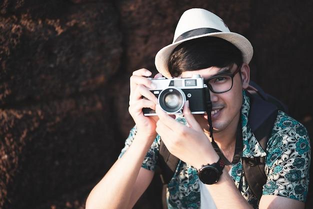 Viaggiatore del fotografo del giovane con lo zaino che cattura foto con la sua macchina fotografica