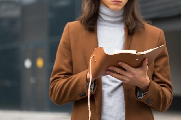 Viaggiatore del primo piano che legge un libro