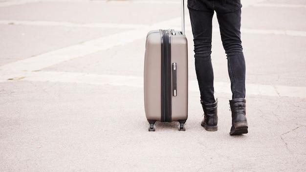Viaggiatore del primo piano che tiene i suoi bagagli