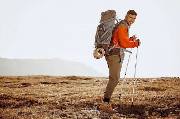 Viaggiatore dell'uomo con bastoncini da trekking salendo per la montagna