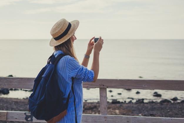 Viaggiatore della donna che cammina sulla spiaggia di vlychada in akrotiri sull'isola di santorini, in grecia. foto di presa turistica del mare