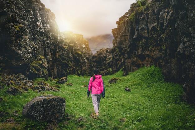Viaggiatore della donna che fa un'escursione attraverso il paesaggio dell'islanda.