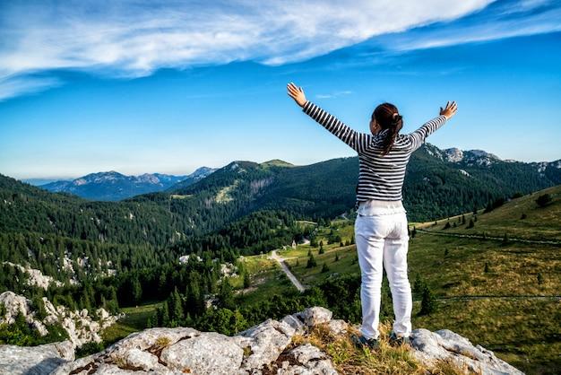 Viaggiatore della donna che fa un'escursione attraverso il paesaggio della croazia.