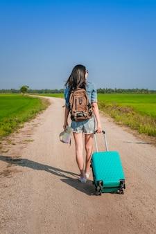 Viaggiatore della donna che rimorchia bagaglio e che cammina sulla strada.