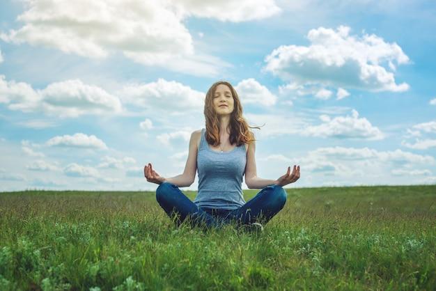 Viaggiatore della donna che si siede sul prato con erba verde sotto il cielo blu con le nuvole nella posizione di loto