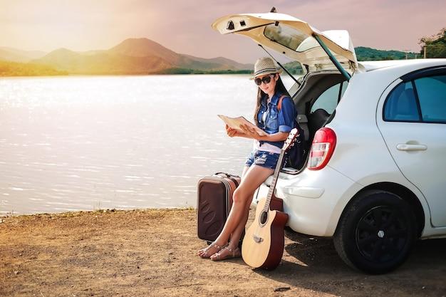 Viaggiatore della donna che si siede sull'autovettura a tre oa cinque porte dell'automobile e che esamina mappa vicino al lago