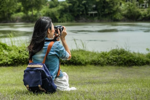 Viaggiatore della donna che si siede sull'erba e che prende la vista della foto della diga