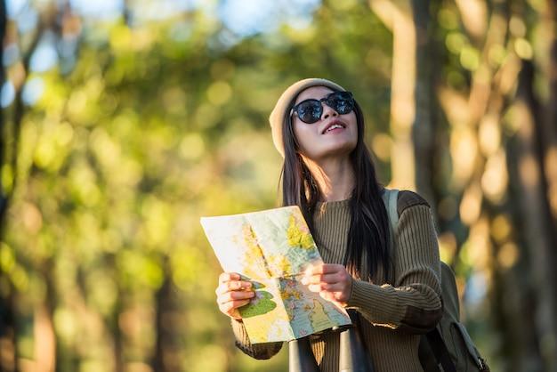 Viaggiatore della donna che va da solo nella foresta
