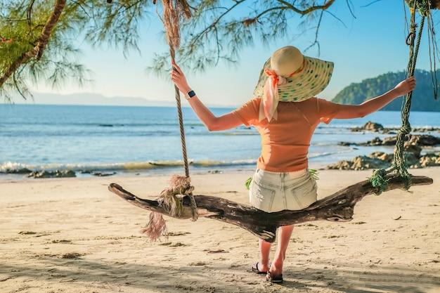 Viaggiatore della donna dell'asia che si siede sull'oscillazione e felice sulla spiaggia.