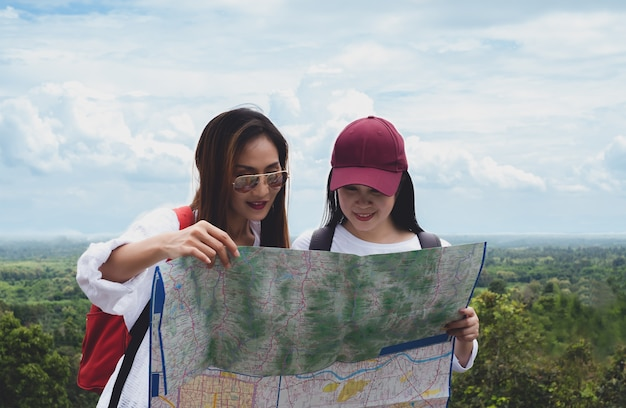Viaggiatore della donna due che guarda mappa sul campeggio della montagna di viaggio