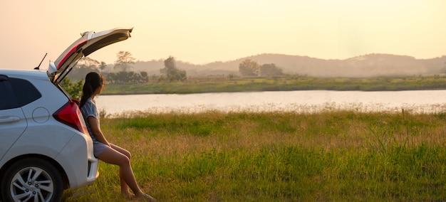 Viaggiatore della donna seduto sulla macchina rilassarsi dalla settimana di lavoro la sera in mezzo alla natura.