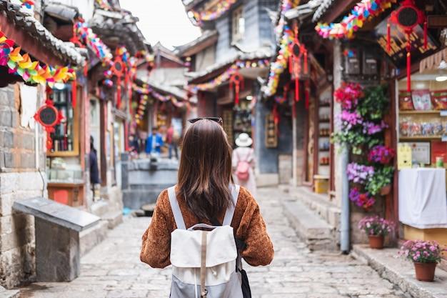 Viaggiatore della giovane donna che cammina alla vecchia città del lijiang in cina, concetto di stile di vita di viaggio