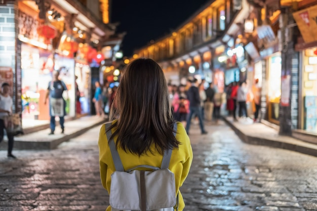 Viaggiatore della giovane donna che cammina alla vecchia città del lijiang in cina, stile di vita di viaggio