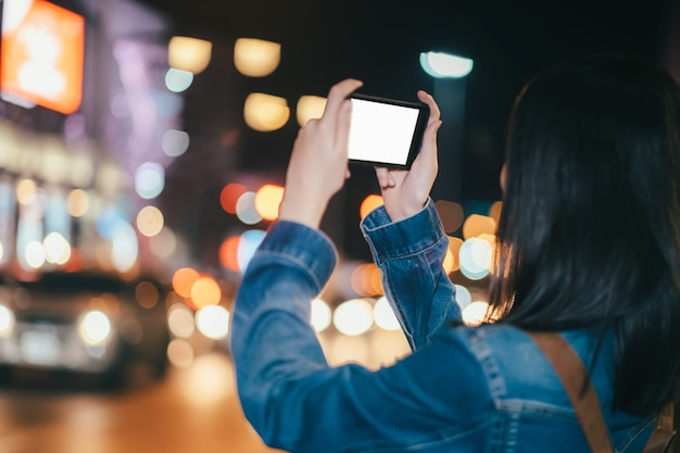 Viaggiatore della giovane donna che prende foto con il telefono cellulare.