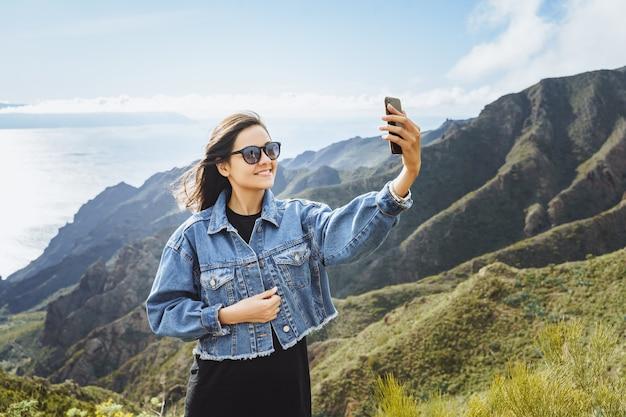 Viaggiatore della giovane donna che prende un selfie facendo uso di uno smartphone