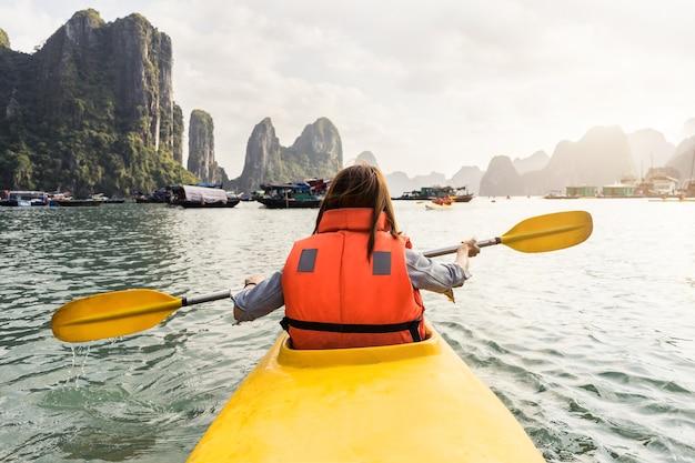 Viaggiatore della giovane donna che rema il kajak nella baia tropicale