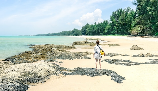 Viaggiatore della giovane donna con la borsa di acqua che gode del giorno soleggiato al saltare dell'isola della spiaggia