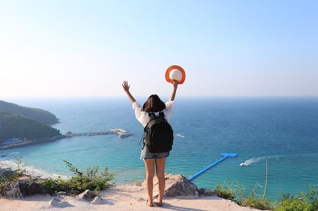 Viaggiatore della giovane donna con lo zaino che gode e che sta sulle montagne