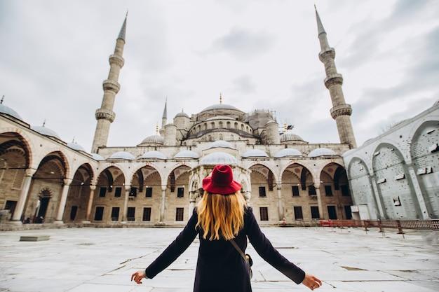 Viaggiatore della giovane donna in cappello e cappotto nero che esaminano la moschea blu a costantinopoli, turchia. una ragazza cammina attraverso l'inverno istanbul. foto della bionda di viaggio sullo sfondo di una moschea il giorno di autunno.