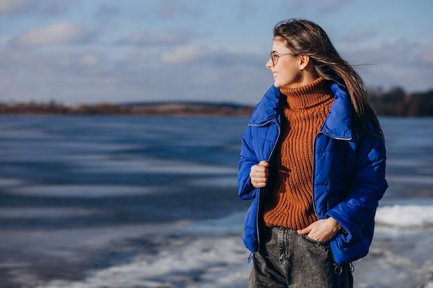 Viaggiatore della giovane donna in giacca blu che guarda il mare