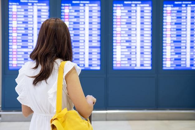 Viaggiatore della giovane donna nell'aeroporto che esamina il bordo di informazioni di volo