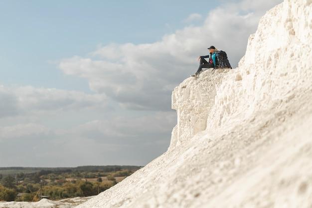 Viaggiatore della possibilità remota che si siede sulla montagna