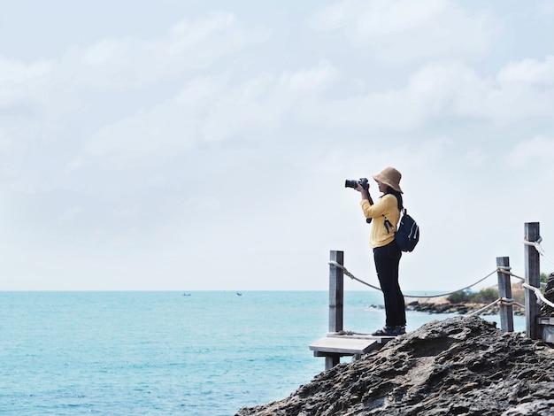 Viaggiatore della ragazza che cattura le fotografie della spiaggia di estate.