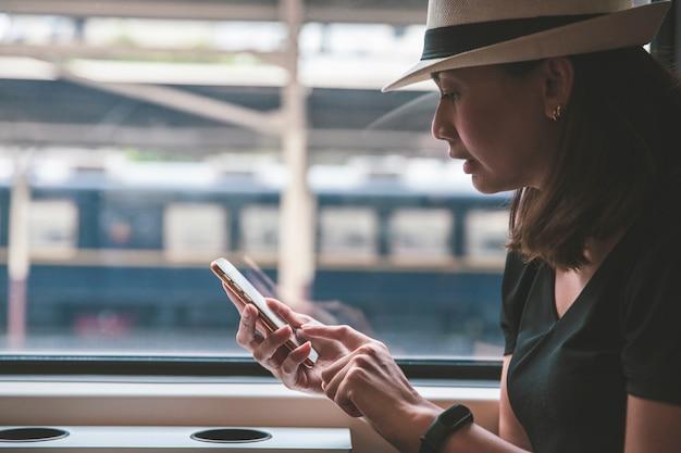 Viaggiatore di bella giovane donna che per mezzo dello smartphone ad una stazione ferroviaria