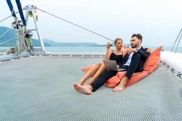 Viaggiatore di coppia rilassante di lusso in bel vestito e suite sedersi sulla borsa di fagioli e guardare al computer