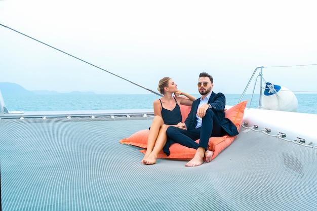 Viaggiatore di coppia rilassante di lusso in bel vestito e suite sedersi sulla borsa di fagioli in parte dello yacht da crociera.