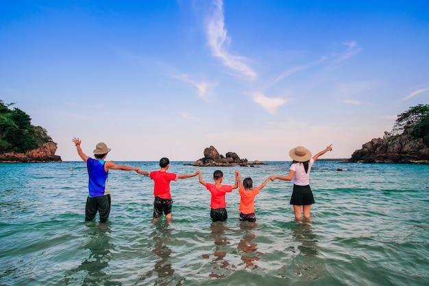 Viaggiatore di famiglia a piedi e godendo sulla spiaggia.