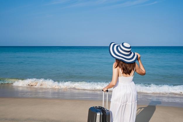 Viaggiatore di giovane donna asiatica con bagagli in spiaggia di sabbia tropicale