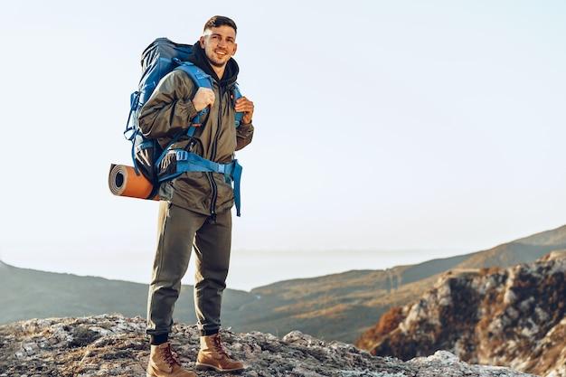 Viaggiatore di giovane uomo caucasico con grande zaino escursionismo in montagna