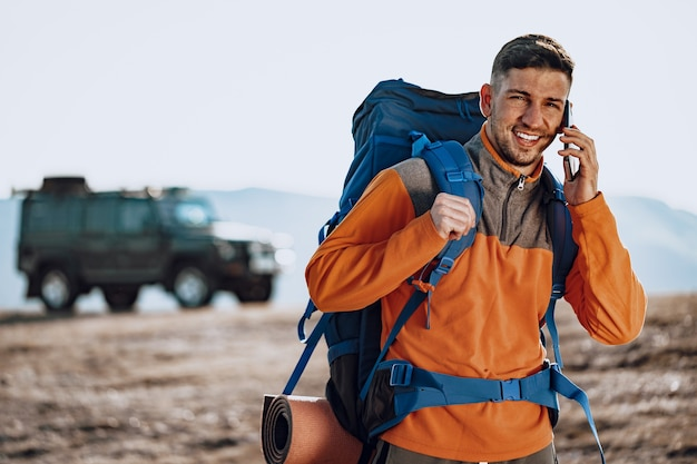 Viaggiatore di giovane uomo caucasico utilizzando il suo smartphone