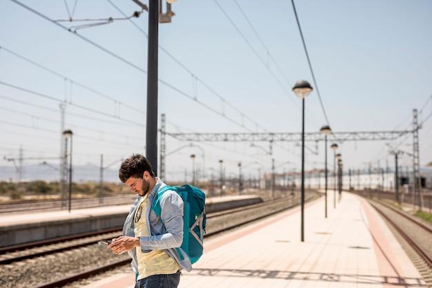 Viaggiatore di medio livello che esamina il telefono