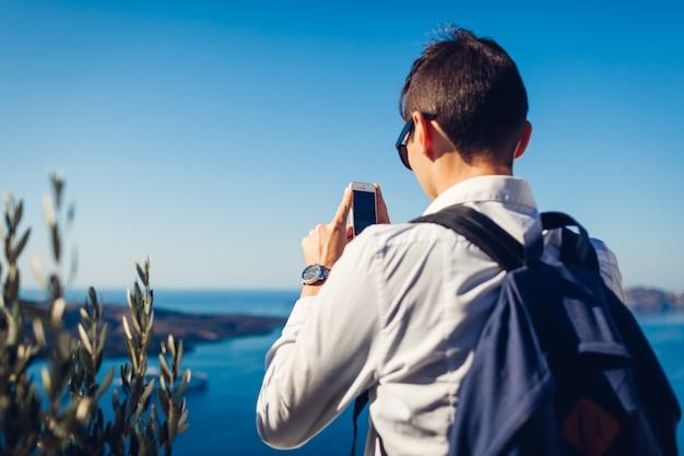 Viaggiatore di santorini che prende foto della caldera da fira o thera, grecia sul telefono. turismo, viaggi, concetto di vacanza