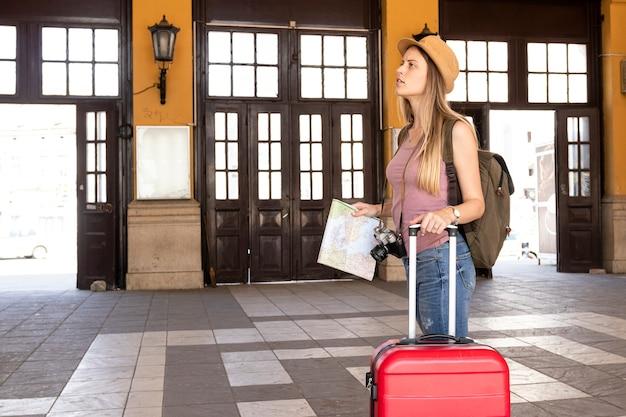 Viaggiatore di traverso che distoglie lo sguardo in una stazione ferroviaria