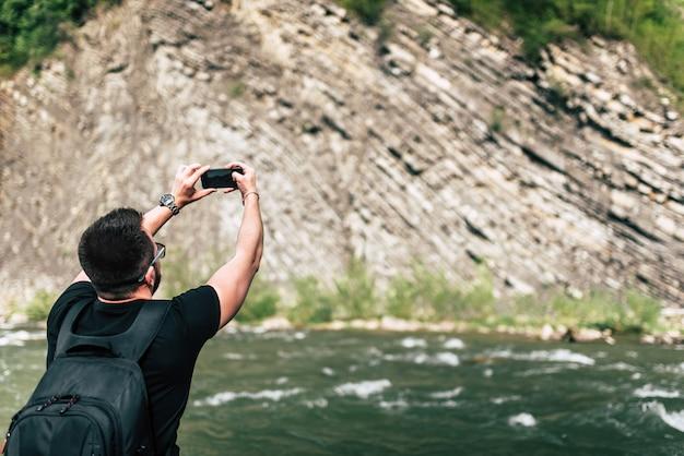 Viaggiatore di yong che prende foto vicino al fiume della montagna