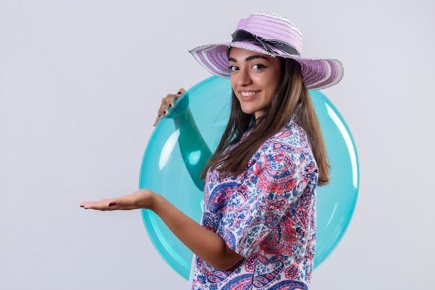 Viaggiatore donna che indossa il cappello estivo che tiene anello gonfiabile sorridente positivo e felice che presenta allegramente con il braccio della sua mano qualcosa in piedi sul bianco isolato