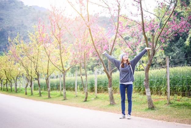Viaggiatore donna felice rilassarsi sentirsi libero con fiori di ciliegio o albero di fiori di sakura