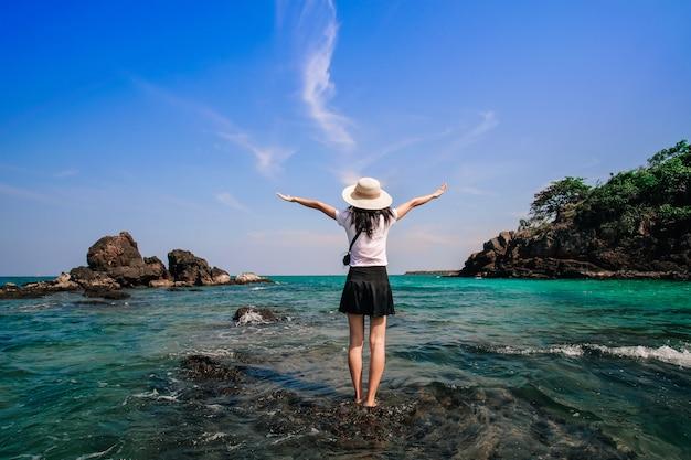 Viaggiatore donna in piedi e felice sulla spiaggia.