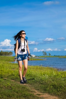Viaggiatore donna in piedi vicino al lago in montagna