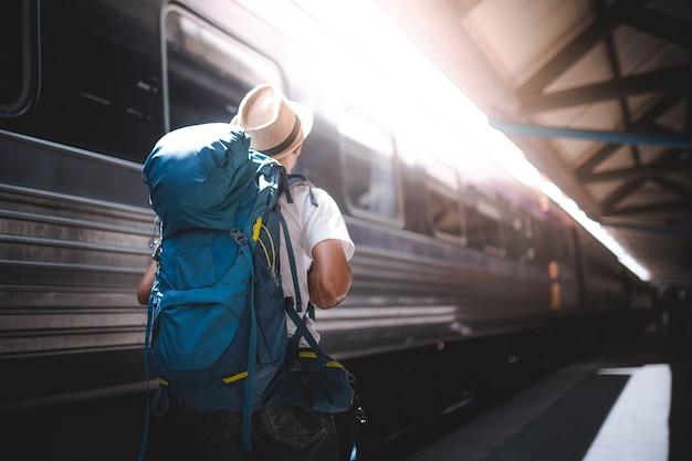 Viaggiatore è zaino in spalla e cammina da solo alla stazione ferroviaria.