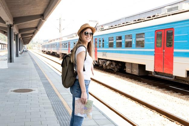 Viaggiatore felice che sorride alla stazione ferroviaria