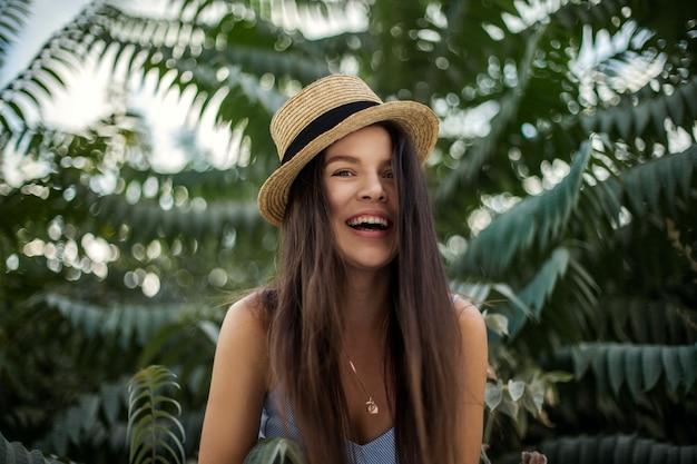 Viaggiatore felice in un cappello su uno sfondo di palme. la ragazza ride e si rallegra