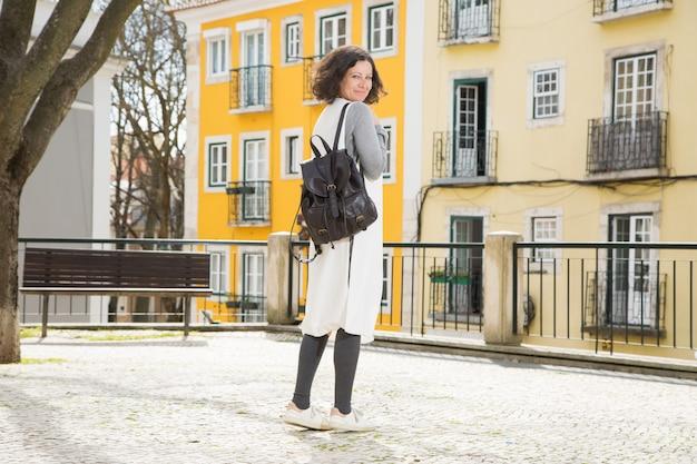 Viaggiatore femminile allegro felice pronto per la passeggiata